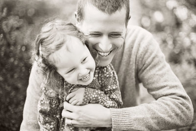 father hugging young daughter from behind while they laugh