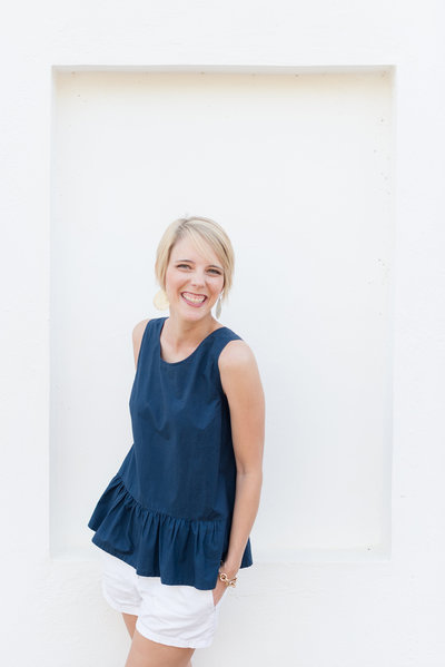 Cassady K Photography laughing in front of a white wall