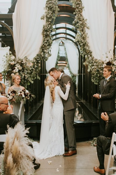 Bride and groom kissing in front of draped arch with eucalyptus garland