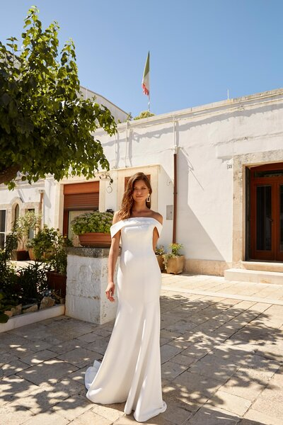 There is an air and lightness to this seasons Madi Lane's crepe collection and if you are a bride not sure where to start, then start with Miles. She is simple and elegant at the front with her straight strapless design which moves into off the shoulder straps, dipping into a V when she turns. Her figure hugging gown skims the hips before fishtailing from her knee and into an indulgent train. Miles is contemporary in her design and brings her regal touch with a detachable cape. Floral embroidered lace works its way around the edging before plunging up the centre of the cathedral length cape – a length which is irresistibly extraordinary in the way it trails behind Miles. It's the modern touch her bride loves when looking for a less traditional option to a veil. Miles has an easy flare of drama as soon as her cape is fastened, making her simplicity all that more exciting.