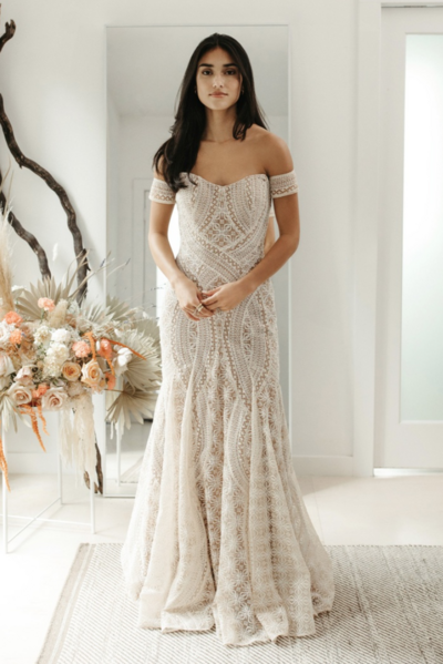 Strapless fit and flare gown paired with detachable armbands. This gown is made from custom perfectly hand-placed embroidery to flatter the body.illusion bodice with hand-placed feather embroidery on a fit and flare Soft net godet skirt. Available in two colors, Ivory/Ivory and Ivory/Nude.