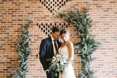 Bride and groom with brick wall