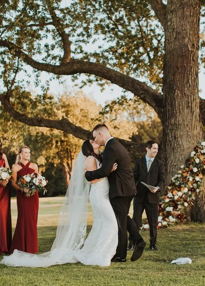 Wedding Ceremony Couple kissing with unique tree floral arrangement