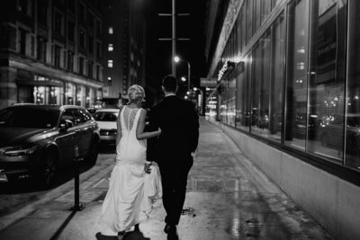 Bride and groom walk down street at night.