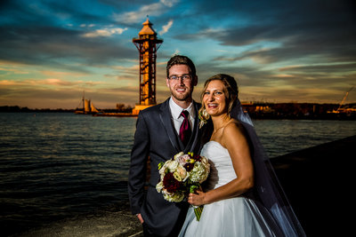 Bride and groom standing outside Sheraton Erie Bayfront Hotel at sunset with Bicentennial Tower in the background