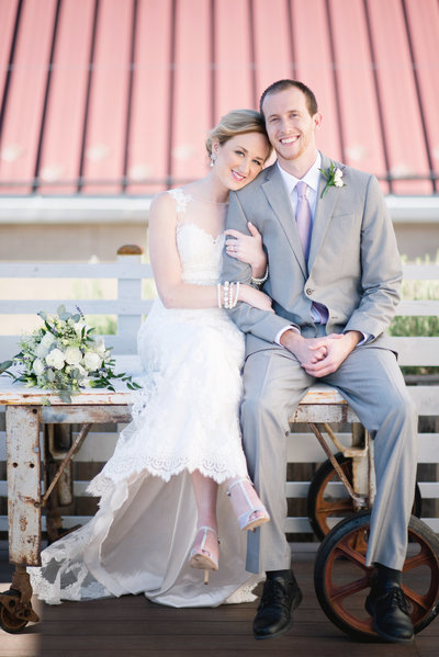 Bride and groom sit atop a rustic table next to their bouquet