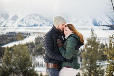 Adventurous couple cuddles in the snow of Grand Teton National Park in Wyoming