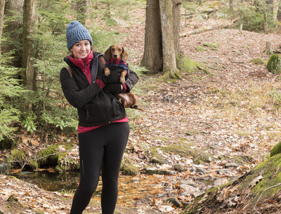 a young lady and a dachshund on a hike