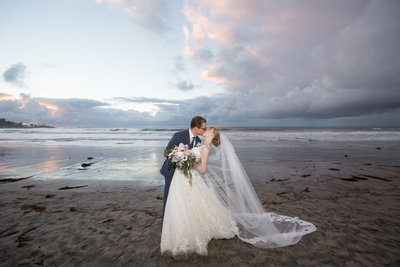 Bride and Groom kissing and dipping with sunset on beach at La Jolla Beach and Tennis Club