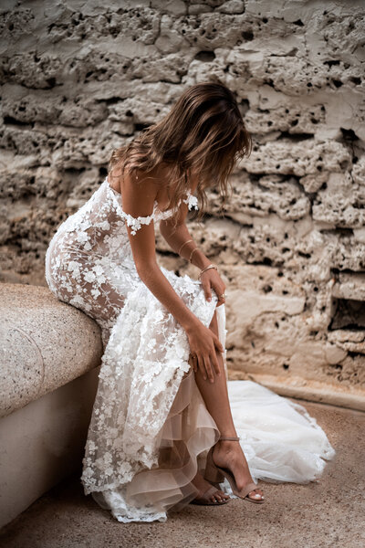 bride-fixing-her-shoe-sitting-by-cobblestone