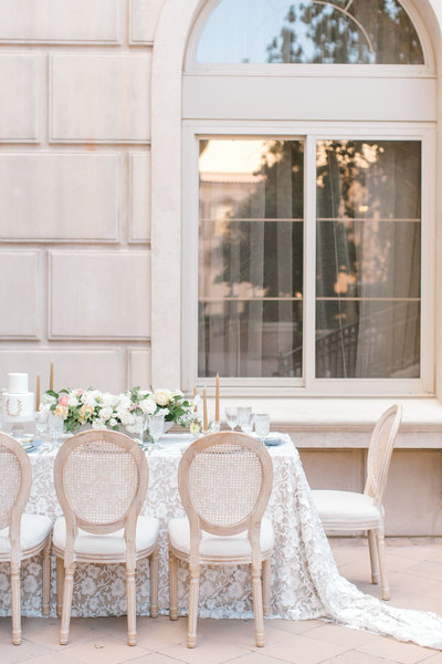 wedding tablescape inspiration with a lace linen, cane chairs and a centerpiece with ivory, peach and a touch of yellow
