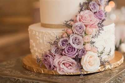 Creme wedding cake with Pink and Purple flower photo.