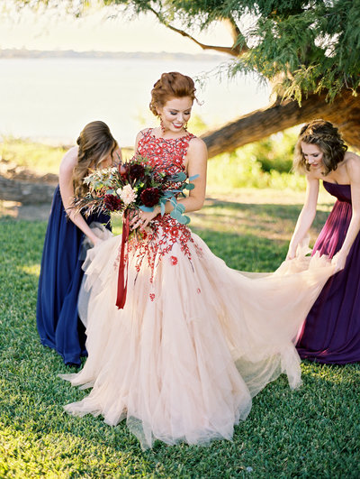 bridesmaids helping bride in red and blush tulle dress with red bouquet