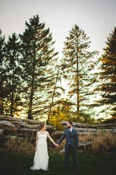 A bride and groom holding hands, sharing a smile as the sun shines through this beautiful rustic setting at Badger Farms in Deerfield Wisconsin for this late fall Wisconsin Wedding.