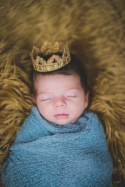 newborn photography session of baby in grey blanket and golden crown