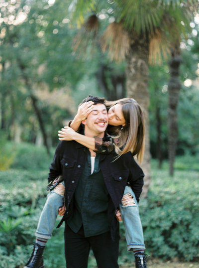 Engaged couple laughs, plays, and kisses while on piggy back in Seville Spain | J.J. Au'Clair