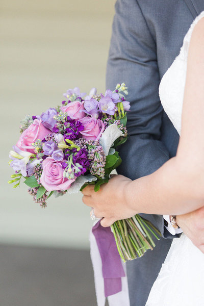 A close up of a bridal bouquet with purple flowers