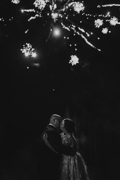 black and white photo of couple kissing against the fireworks