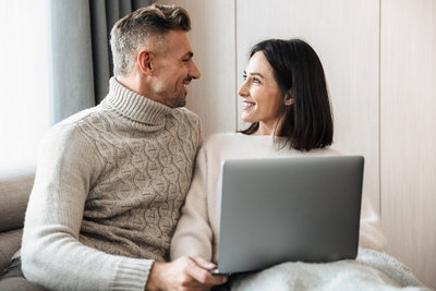 A Couple smile at one another as they listen to something on their laptop. This could symbolize what a teletherapy session might look like from the comfort of your home. We offer online marriage counseling, online relationship therapy, and more.