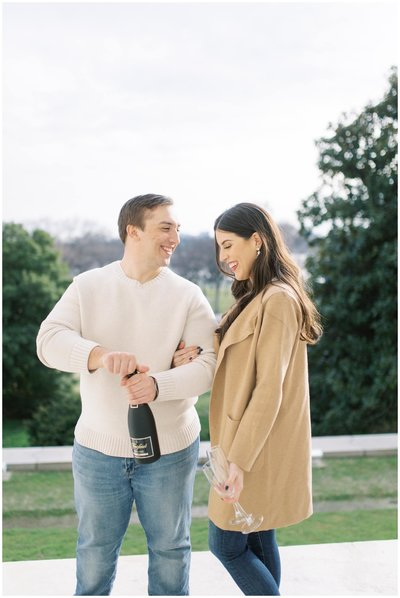 Engaged couple opening a bottle of champaign during engagement session.