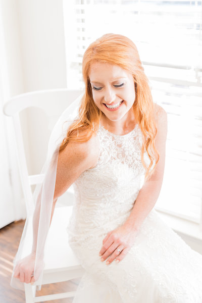 Bride with red hair and lace dress posing by window