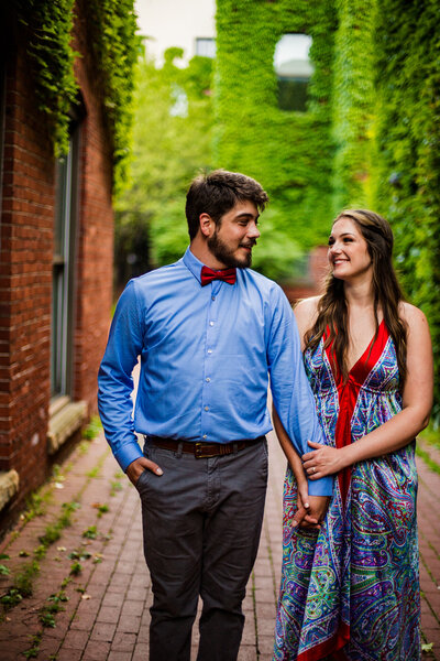 Couple holding hands and walking through Modern Tool Square for engagement photos  in Erie, PA