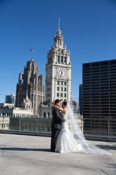 Bride and groom photo on a rooftop in downtown Chicago that show The Wrigley Building  tower in the background.