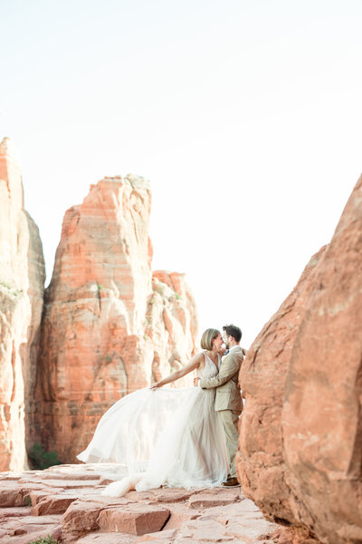 A bride kisses her groom up against red rock cliffs in Sedona during their elopement