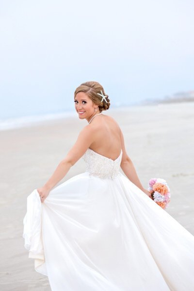 bride swings dress in bridal portrait on the beach at huntington beach state park in south carolina