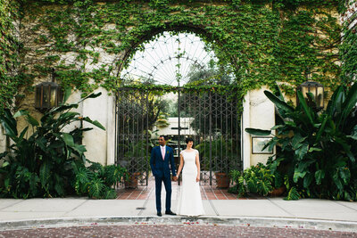 Sophisticated couple hold hands in front of ivy covered gate on their wedding day