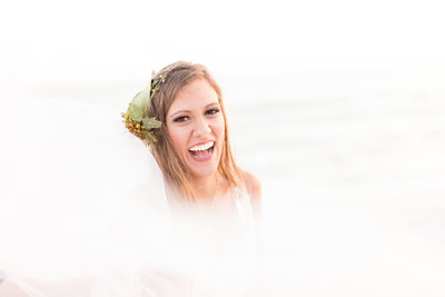 Bride laughs towards camera on beach.