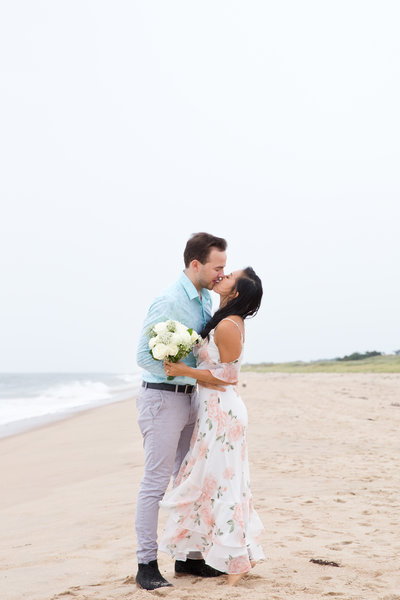 Couple kiss on the beach in the rain in the Hamptons after their beach elopement.