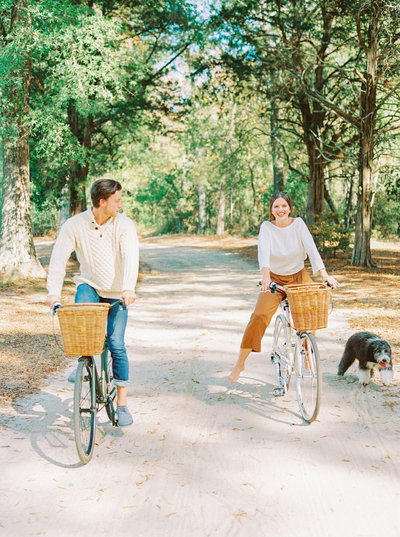 Engaged couple riding bicycles with baskets with their dog