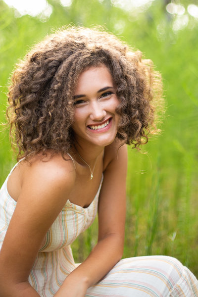 Teen girl smiles for the camera outdoors during senior portraits