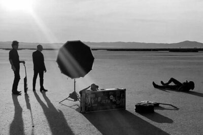 black and white bts photo Mark Maryanovich lying on ground while photographing 7Horse standing in desert guitar and case beside reflector in front of them