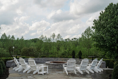Adirondack chair circle around fire pit outside modern farmhouse with a view