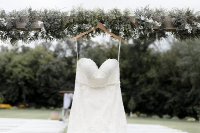 Lace Strapless Wedding Dress hanging from seeded eucalyptus on a white barn door at Ridgetop in Prescott Wisconsin