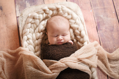 Beautiful Mississippi Newborn Photography: sleeping newborn boy  wrapped in brown in a wooden dough bowl