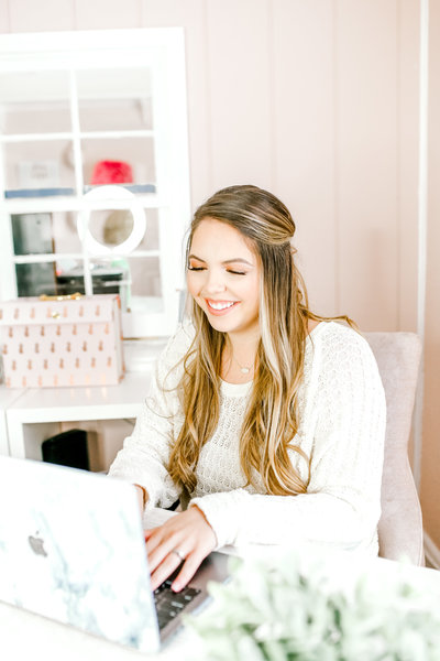 Female entrepreneur smiling using a laptop in pink office