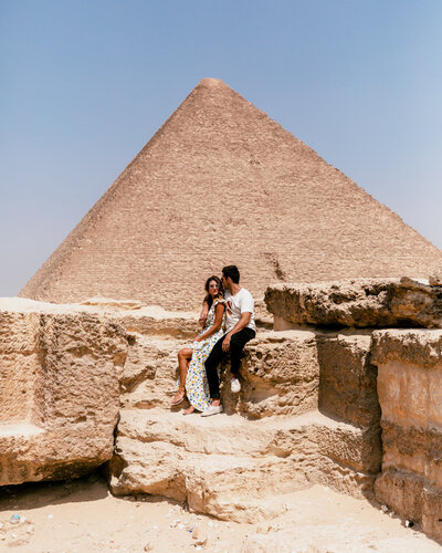 man and woman sitting in front of egyptian pyramid