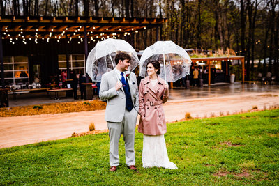 Bride and groom pose in the rain at the Meadows Raleigh