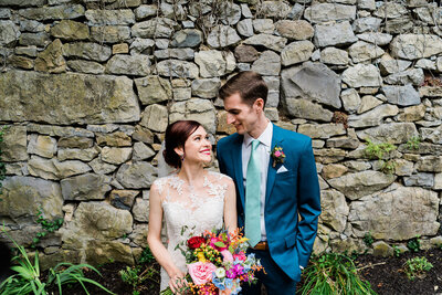 Bride and groom look lovingly at each other in front of garden wall holding bouquet