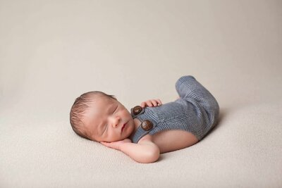 newborn boy in blue suspenders on a tan blanker
