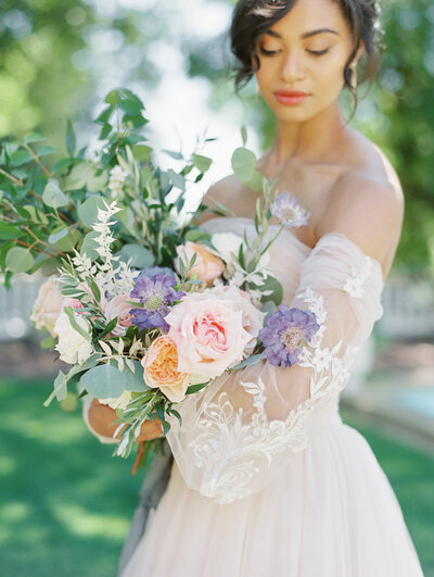 Bride wears strapless gown outside holding spring bouquet