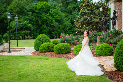 Bridal portrait of Maryn twirling in front of a private venue