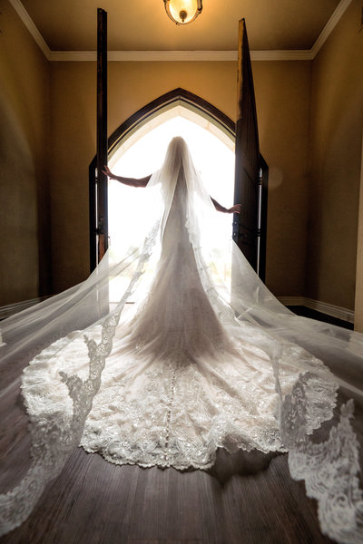 bride holding the doors open while sunlight pours from outside