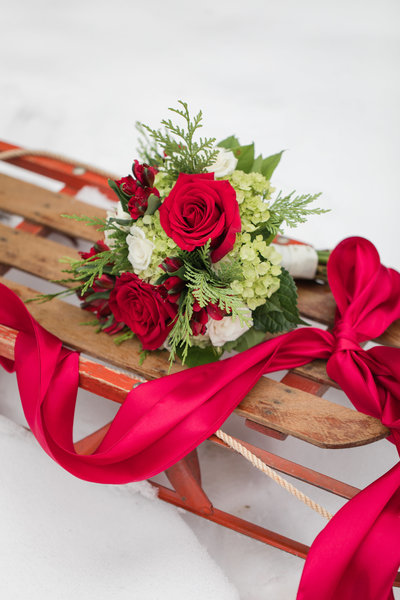 winter wedding bouquet on an antique sled at the Golden Horseshoe Inn wedding venue