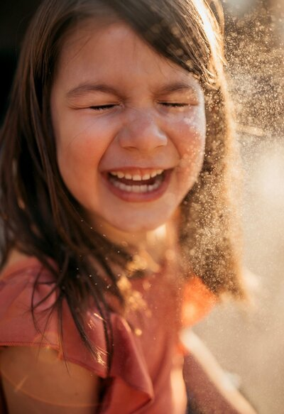 girl laughing with water spalsh