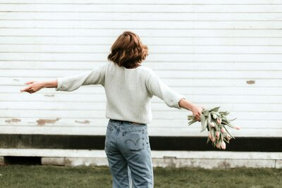 Woman in jeans holding a bouquet of flowers and twirling