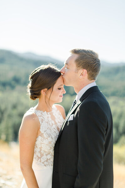 groom kissing brides forehead with mountains in the background
